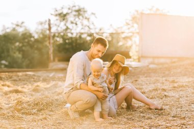 family with adorable son spending time together at countryside