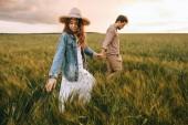 elegantní pár drží za ruce a chůzi na zelené louce