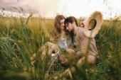 beautiful stylish couple hugging in green grass on meadow