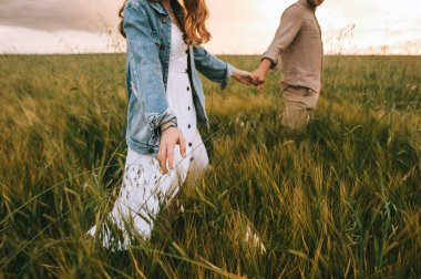 cropped view of couple holding hands and walking on green summer meadow