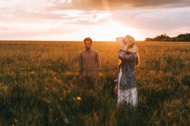 young stylish couple walking on summer meadow at sunset with back light