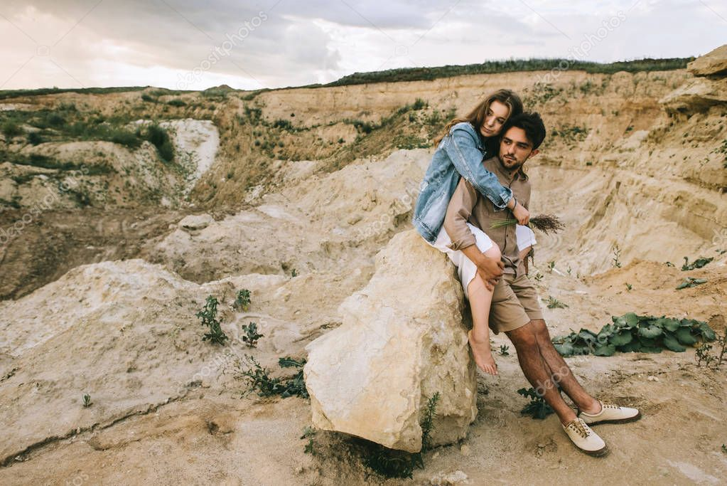 young beautiful couple embracing and sitting on rock in canyon