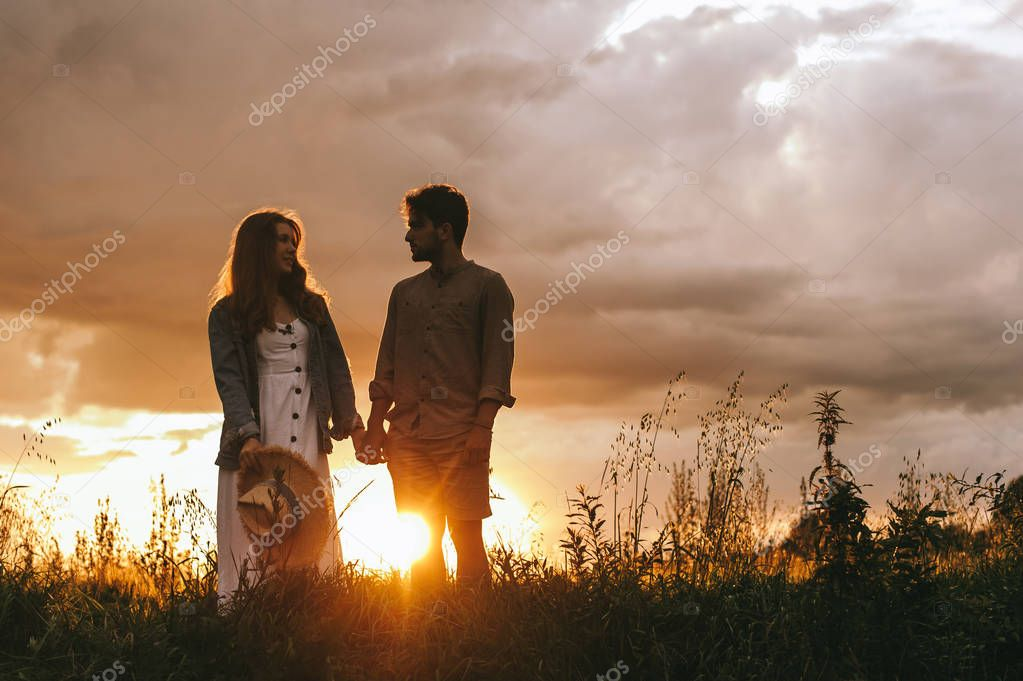 silhouette of couple holding hands on meadow at sunset