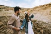 Fotografie Smějící se dívka, zavřel oči a drželi se za ruce s v písku canyon