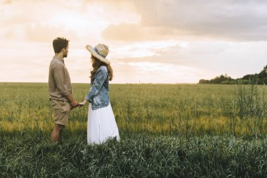 stylish couple holding hands on green field and looking at sunset