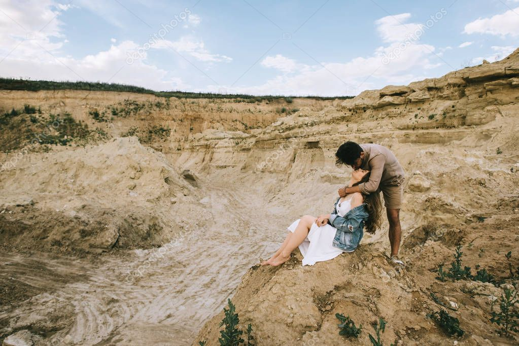 stylish man hugging and kissing girlfriend in sand canyon