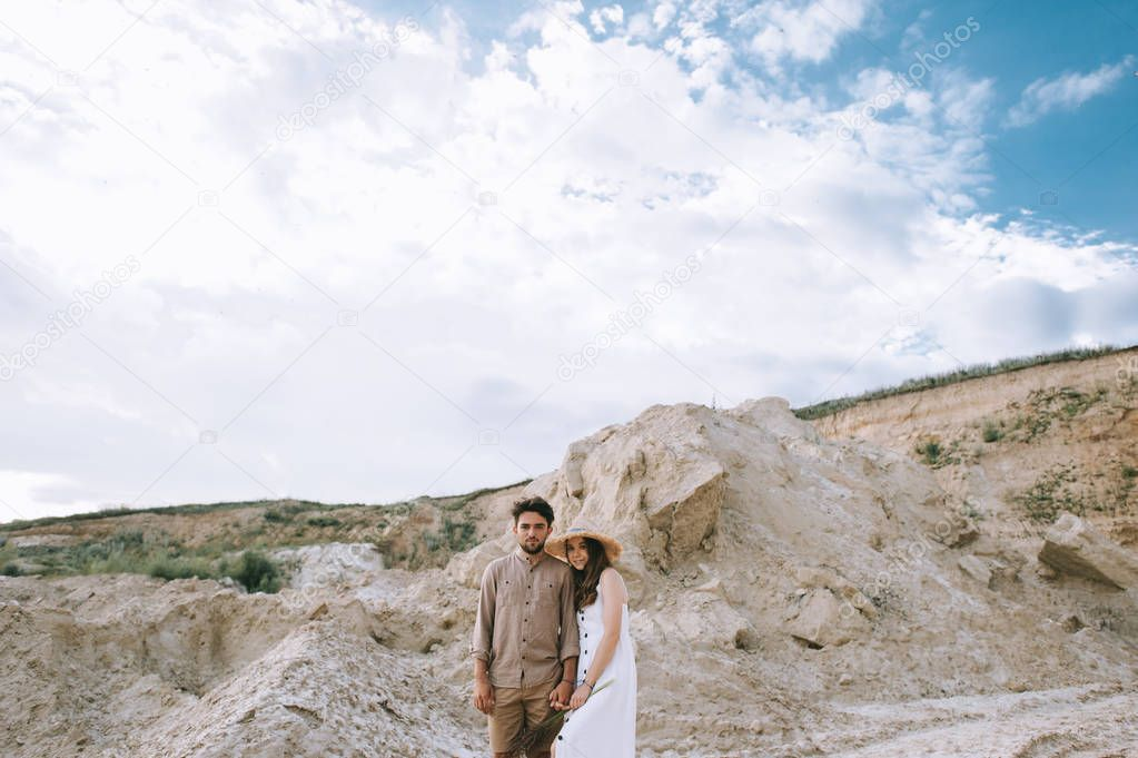 couple holding hands and standing in sand canyon with cludy sky