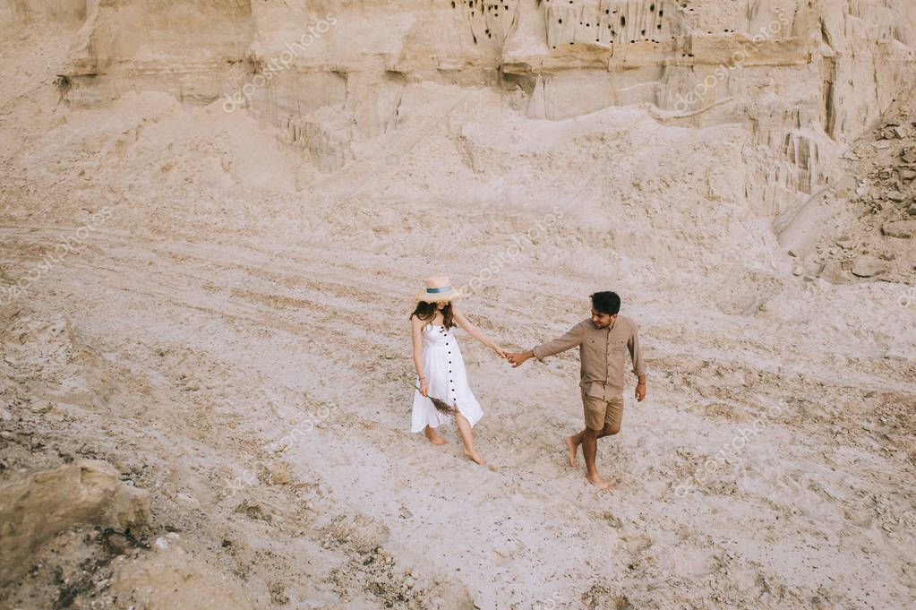 high angle view of couple holding hands and walking in sand canyon