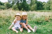 Fotografie rozkošné děti v slaměné klobouky v poli