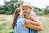 Mutter umarmt Tochter im Sommerfeld