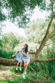 Fotografie stylish mother and daughter sitting on tree trunk together