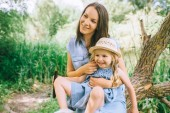Fotografie smiling mother and adorable daughter spending time together in nature
