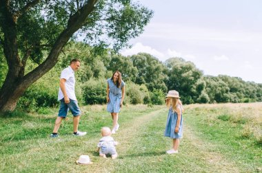 happy family with two kids spending time together on summer feild