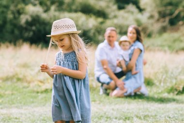 little girl in straw hat in summer feild with family behind
