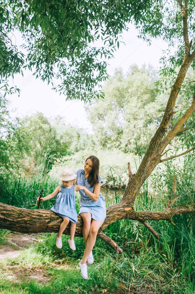 stylish mother and daughter sitting on tree trunk together