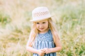 Fotografie adorable blonde child in dress and straw hat
