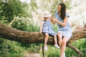 mom and daughter sitting on tree and spending time together in nature