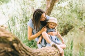 mother and adorable daughter hugging and sitting on tree trunk