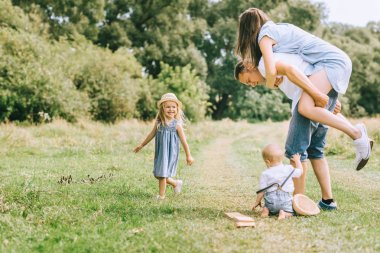 family with children spending time on summer feild, father piggybacking mom