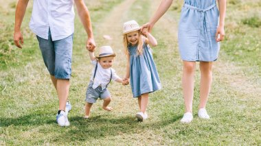 parents with two children holding hands and walking on summer feild