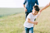 Photo cropped image of parents and son running on field