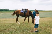 parents standing near horse, smiling son looking at camera on field