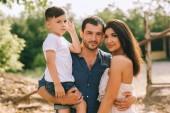 Fotografie portrét rodičů a syn při pohledu na fotoaparát venku