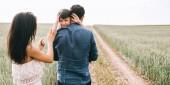 matka a syn mává rukama na cestu v poli