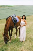 Fotografie beautiful woman standing with brown horse and looking at camera on field
