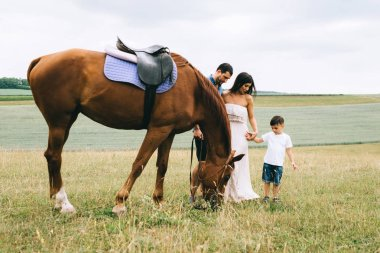 parents and son standing near beautiful brown horse on field
