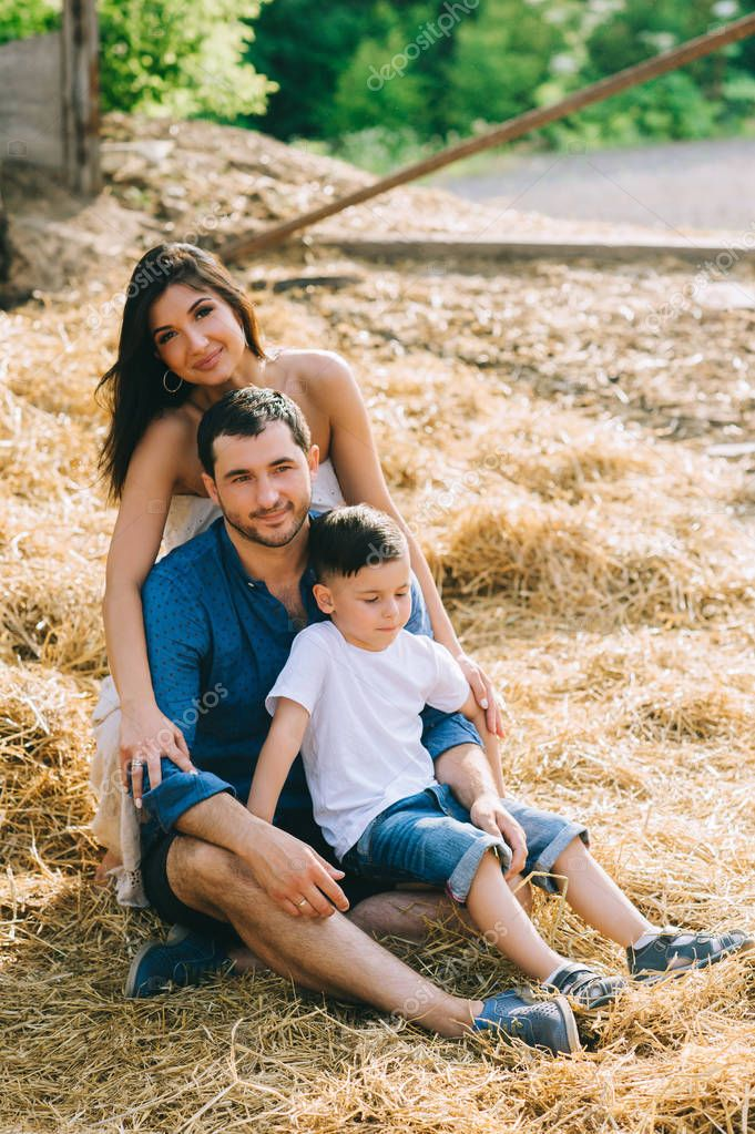 cheerful parents and son sitting on hay at village