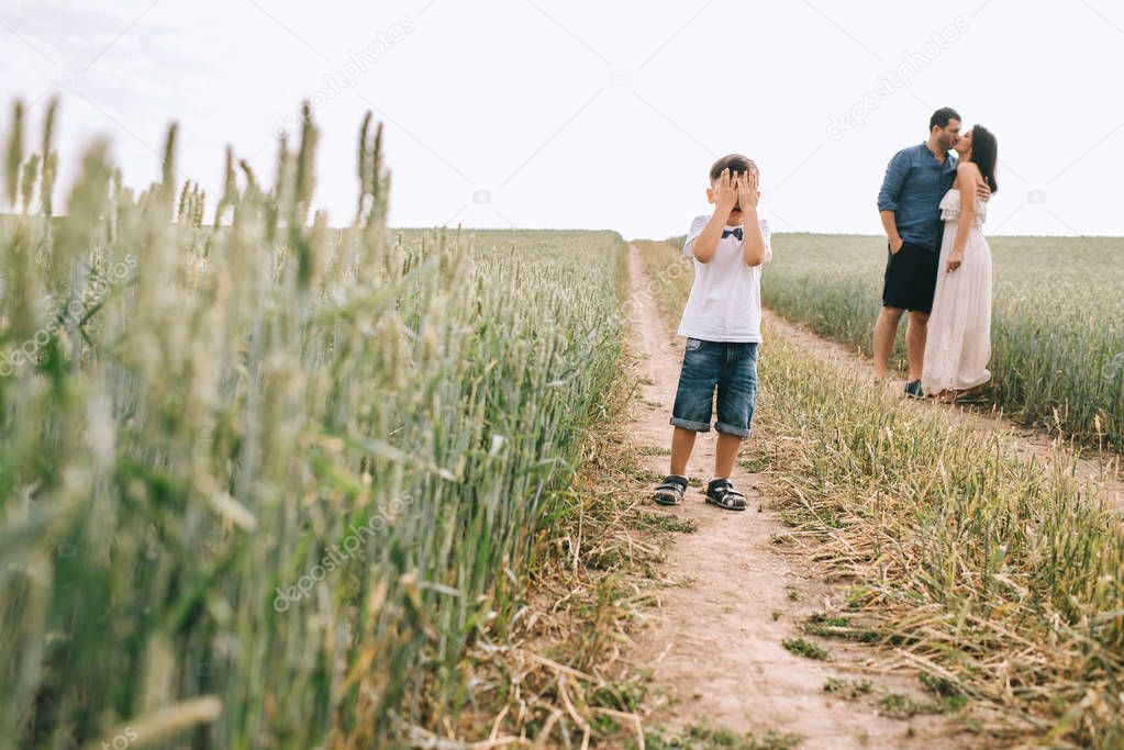 parents kissing and son covering eyes on path in field