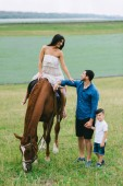 Fotografie mother riding horse and father with son standing on field