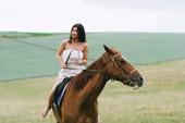 krásná žena na koni hnědého koně na zeleném poli