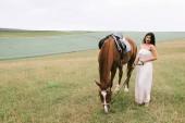 Fotografie beautiful woman standing near brown horse on field