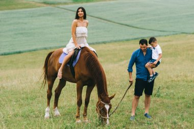 mother riding brown horse and father with son standing on field