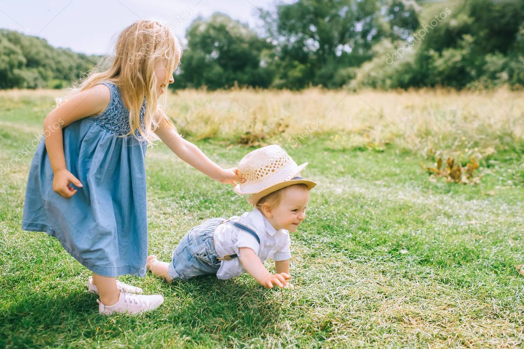 adorable blonde siblings playing in green field