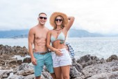 Fotografie smiling couple in sunglasses standing at beach in Montenegro