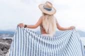 Fotografie zadní pohled na dívku v slaměný klobouk drží deku na pláž v Černé hoře
