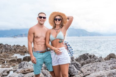 smiling couple in sunglasses standing at beach in Montenegro