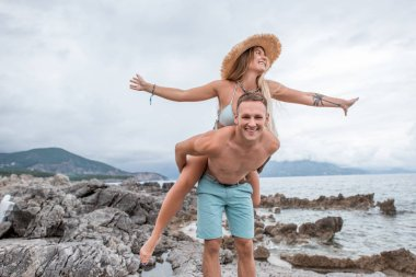 happy young couple piggybacking and having fun on rocky beach in montenegro