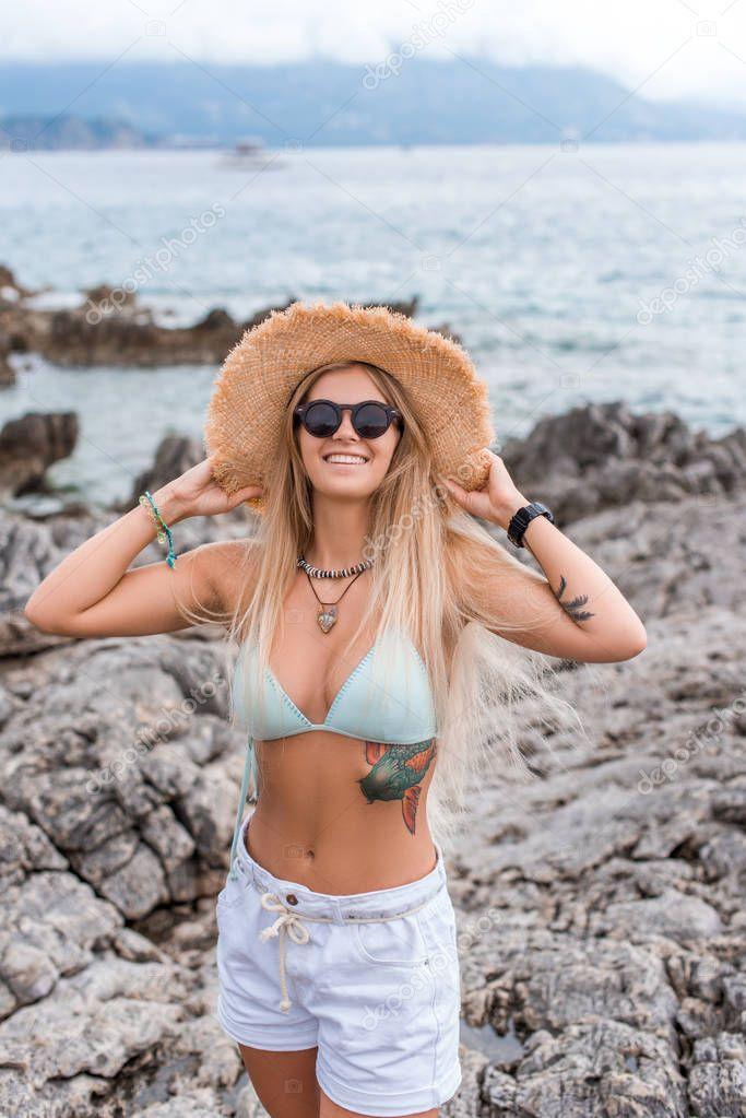 beautiful girl in bikini top touching straw hat at beach in Montenegro