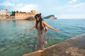 Žena na straně přístaviště s Stari Grad (staré město) na pozadí v Budva, Černá Hora