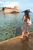 žena stojí na molu se Stari Grad (staré město) na pozadí v Budva, Černá Hora