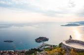 žena sedí na pohledu a při pohledu na ostrově Sveti Stefan při západu slunce v Budva, Černá Hora