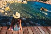 zadní pohled na ženu sedící na mostě poblíž moře v Budva, Černá Hora
