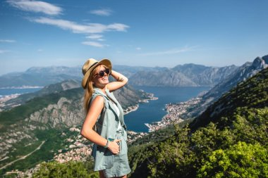 smiling woman posing with beautiful view on Kotor bay in Montenegro