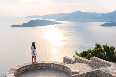 woman standing on viewpoint near Adriatic sea during sunset in Budva, Montenegro