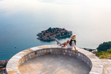 Woman sitting on viewpoint near saint stephen island in Adriatic sea, Budva, Montenegro stock vector