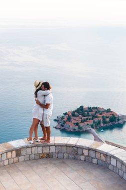 couple hugging on viewpoint near island of Sveti Stefan with hotel resort in Adriatic sea, Budva, Montenegro